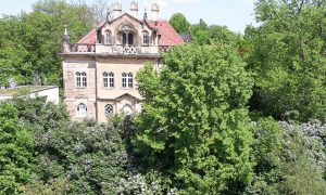 The Waldschlösschen framed by lilac flowers as it can be seen from our terrace.